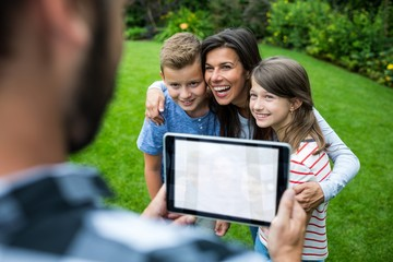 Father clicking picture of family from digital tablet in park