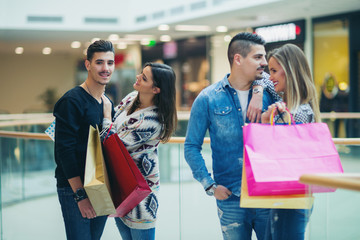 Group Of Young Friends Shopping In Mall Together