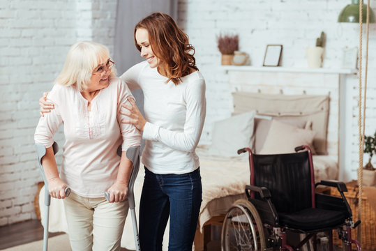 Pleasant caring woman helping with rehabilitation her disabled grandmother