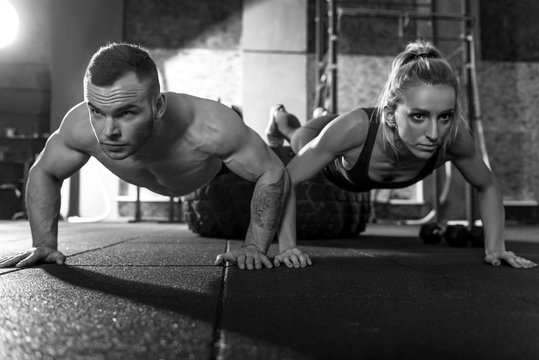 Strong athletic man and woman doing push ups