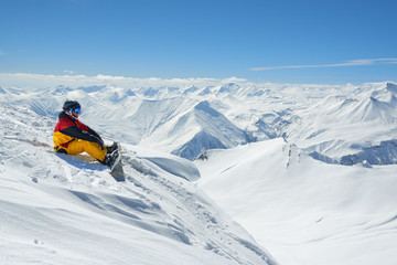 snowboarder sits high in mountains on the edge of slope
