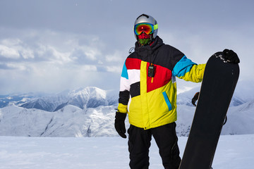 Snowboarder carries a board in  hands.