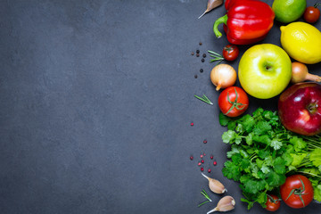 Fresh organic vegetables, fruits and spices on stone background with copy space for text. Top view, horizontal composition