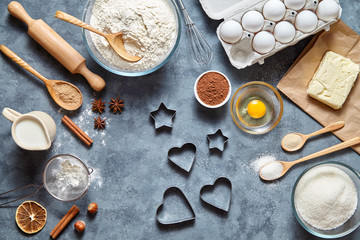 The process of making gingerbread heart on Valentine's Day. Baking ingredients for homemade pastry on dark background. Bake sweet cake dessert concept. Top view, flat lay style
