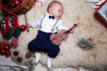 little boy dressed as a gentleman is sleeping with violin under the Christmas tree
