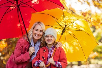 Girl holding umbrella with mother at park