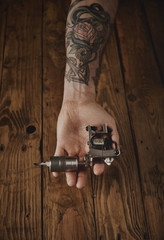 Close up of a man's hand offers new custom made shiny metal tattoo gun on camera, above rustic wooden table