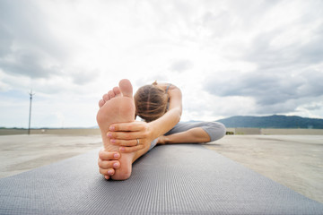 Yoga on rooftop. Young woman stretching on roof with city and mountains view.