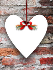 Blank heart shaped ornament frame hanged by red Christmas ribbon against weathered brick wall background