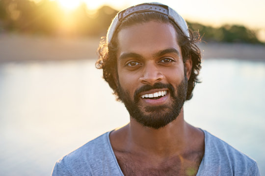 Handsome and confident. Outdoor portrait of smiling young african man at the beach.