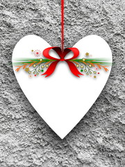 Blank heart shaped ornament frame hanged by red Christmas ribbon against rough gray concrete wall background