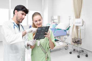 Doctor examining an x-ray film and discussing with a patient