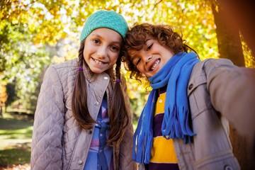 Cheerful siblings taking selfie in park