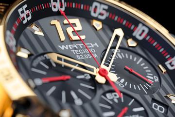 Golden, luxury men's wristwatch. Clock face close up.