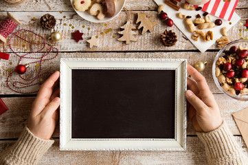 Christmas composition. Man holding picture frame. Studio shot.