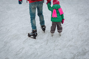 father and little daughter feet learning to skate in winter