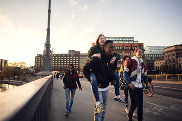 Happy teenage boy piggybacking friend while walking on bridge in city