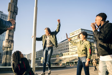 Low angle view of teenagers dancing at town square against clear sky