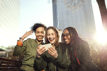 Smiling multi-ethnic friends taking selfie with smart phone in city