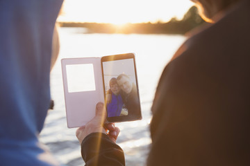 Rear view of man and boy looking at photograph in smart phone against lake