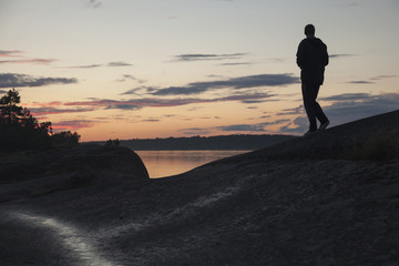 Man standing on rock at lakeshore against sky during sunset