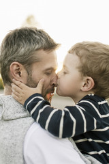 Close-up of son kissing father's nose against clear sky