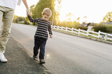 Boy walking with father on empty road