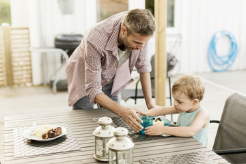 Father feeding son while standing at restaurant
