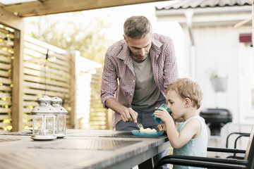 Father talking with son to have food at while standing at restaurant