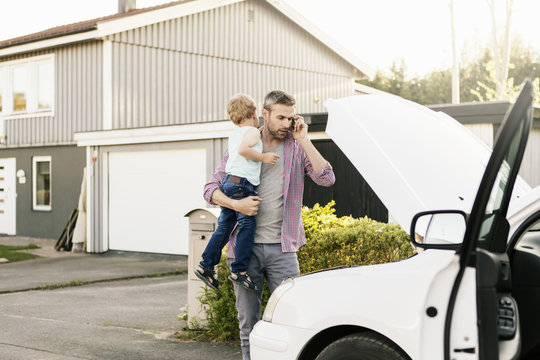 Father carrying son while talking on phone looking at broken down car on street