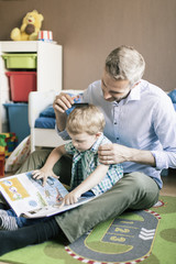 Boy reading book while father combing his hair on floor at home