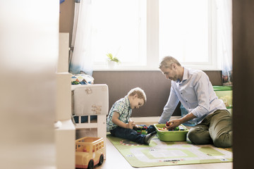 Father playing with son while sitting at home