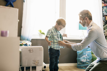 Father dressing up son in brightly lit room at home on sunny day