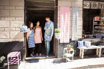 Man and women wearing aprons talking while standing at entrance of fabric shop