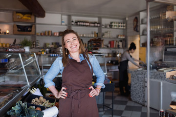 Portrait of smiling woman standing with hands on hip at store