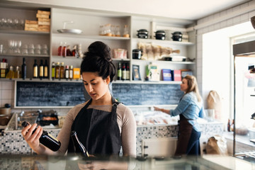Confident woman checking bottles while colleague standing in background at retail display