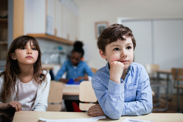 Concentrated children sitting at desk in classroom