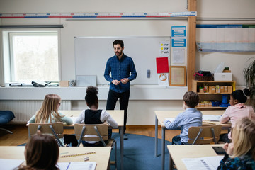 Confident teacher explaining students in classroom at school