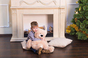 Child boy playing with soft toy bear under the Christmas tree.