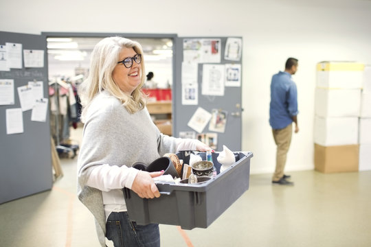 Smiling volunteer carrying crate while walking at workshop