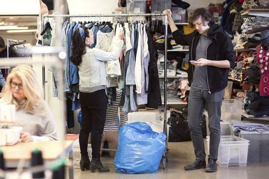Man using phone while woman searching clothes for clothes rack at workshop