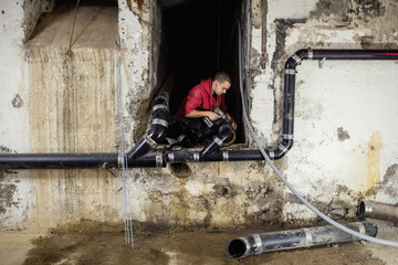 Male plumber connecting pipes amidst walls in basement
