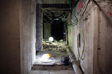 Illuminated lights on floor in messy corridor at construction site