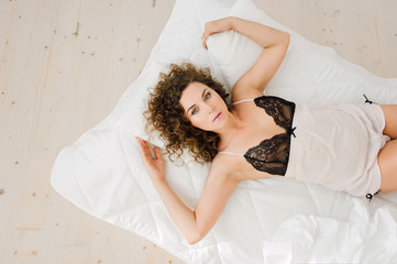 Sexy woman in bed in the morning showing her beautiful body. Awaken with natural light in her bedroom and covered with the bed sheets. Retouched photo.