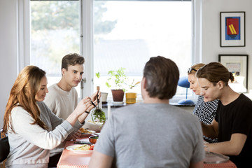 Family having meal at dining table in new house