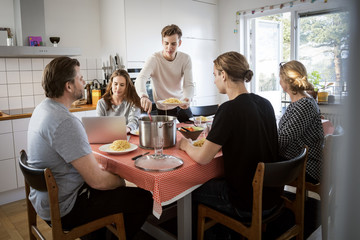 Man serving food for family at dining table