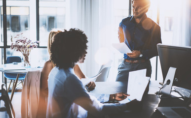 Young team of coworkers making great business discussion in modern coworking office.Hispanic businessman talking with partners.Teamwork people concept.Horizontal, blurred background, flares.