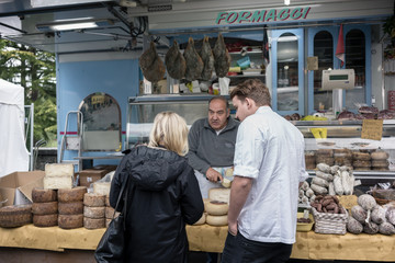 Chef and woman testing meat and cheese at Italian food market st