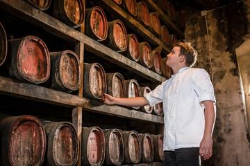 Wine cellar full of vin santo in oak barrels dessert wine aging,
