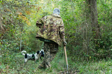Truffle hunter and his dog walking through the woods searching f